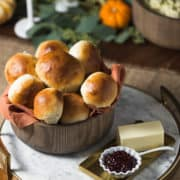 wooden bowl filled with fluffy dinner rolls with a side of jam and butter
