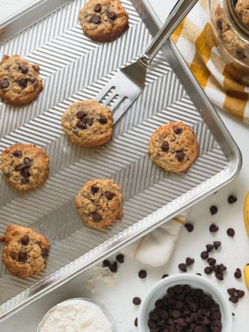 overhead of cookies on a cookie sheet surrounded by scattered chocolate chips, bananas, flour, and a jar of cookies