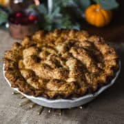 rustic apple pie in a white pie plate surrounded by pumpkins and greenery