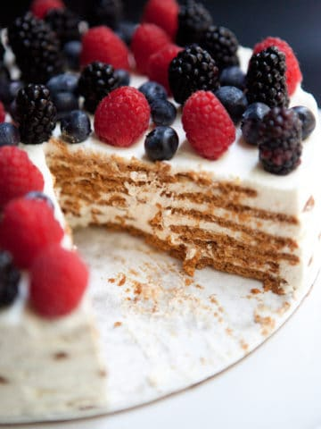Full icebox cake topped with strawberries, blueberries, and blackberries, with a slice taken out so you can see the wafer layers