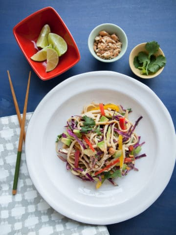 thai peanut noodle bowl on a white plate with peanuts, cilantro, lime wedges and chop sticks
