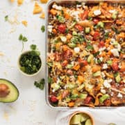 vegetarian sheet pan nachos with black beans, cotija cheese, sweet potato, cilantro, avocado, and tomoatoes