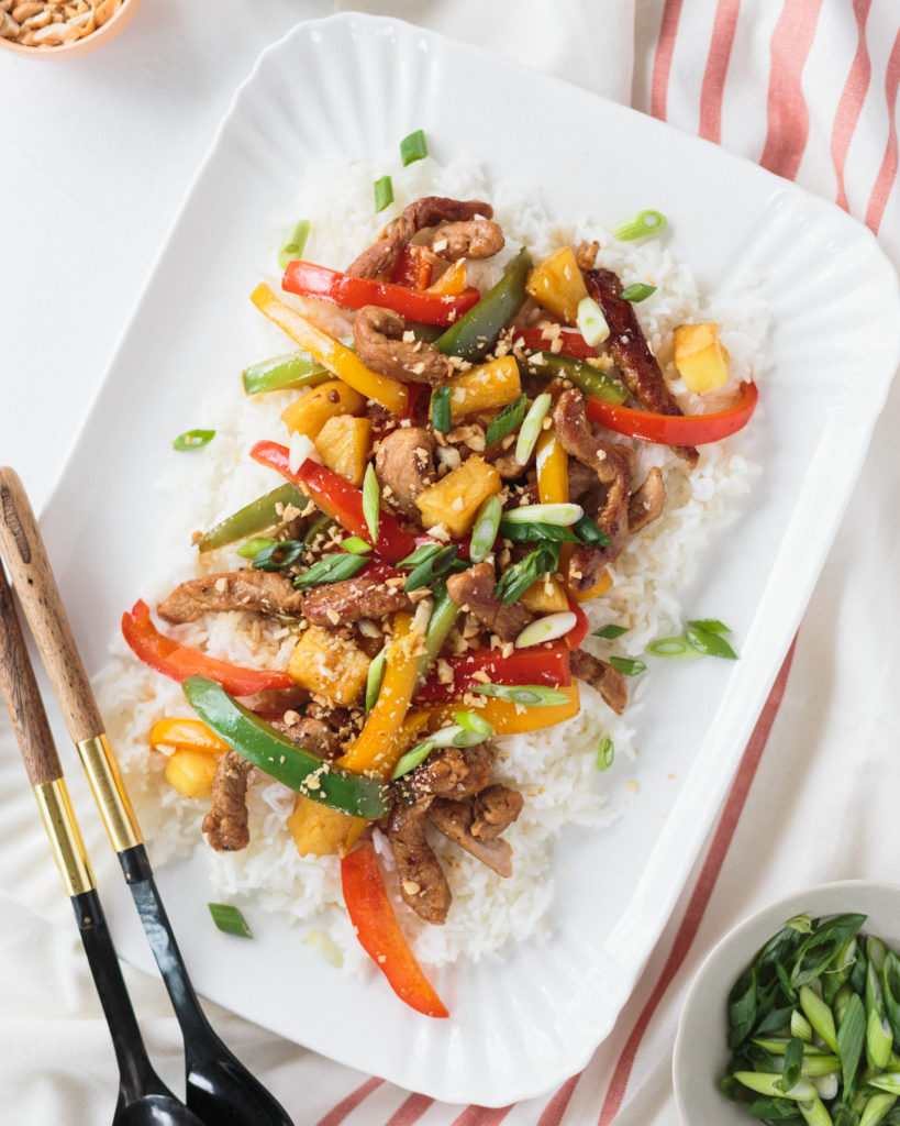 pork and pineapple stir fry with red, green, and yellow bell peppers atop a bed of white rice, on a white platter
