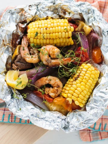 turf and turf dinner with corn on the cob unwrapped in tin foil