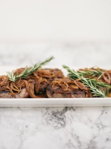 pan seared steak on a white platter with shallots and fresh rosemary