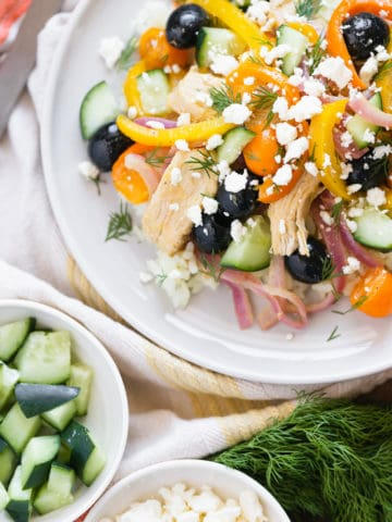 plate with white rice, stir-fry, orange and yellow peppers, feta cheese, cucumber, cherry tomatoes, black olives, fresh dill, and red onion