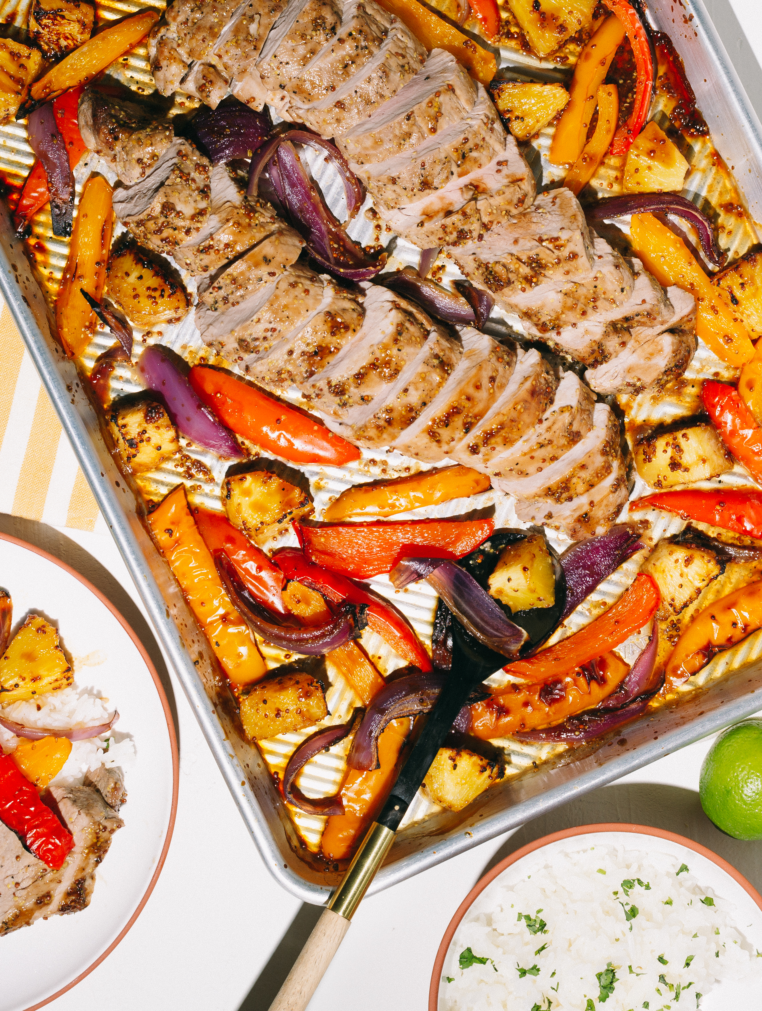 sheet pan pork tenderloin with red and yellow peppers onions and pineapple